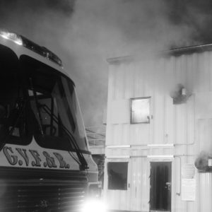 Fire truck in front of burn building at night