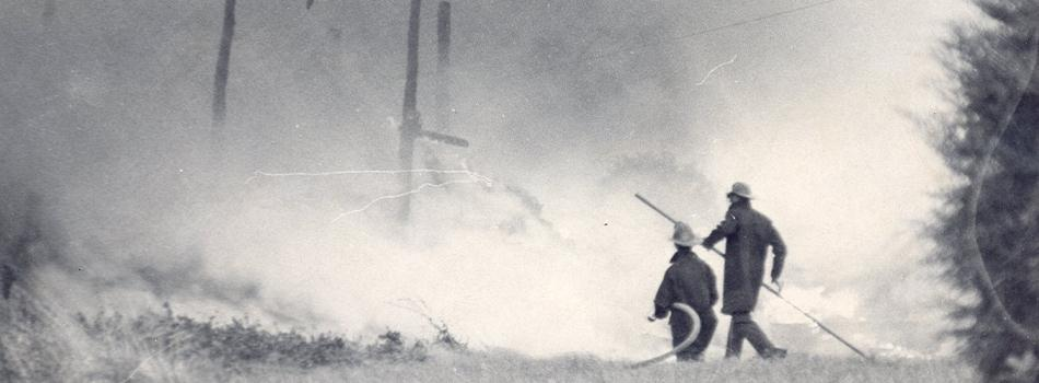 Black and white photo of firefighters fighting a large brush fire